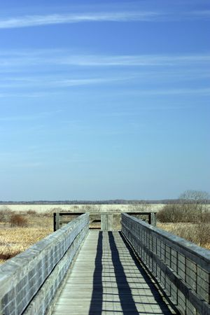 expansive: A boardwalk overlooking a prairie and an expansive, blue sky.