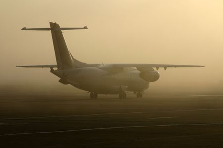 early fog: A regional jet airliner taxiis into the fog on its way to an early morning departure. Stock Photo