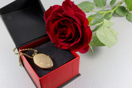 locket: Red rose and golden locket in a gift box Stock Photo