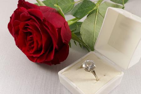 Primer plano de la rosa roja y caja blanca con el anillo de compromiso de oro