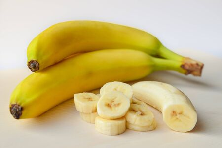 Bananas on a white cutting board