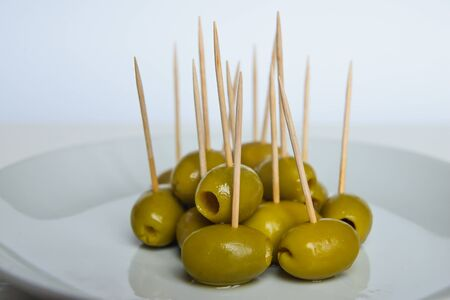 Green olives with toothpick, on a white plate