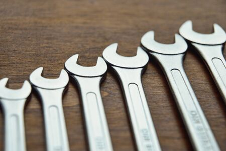 Metal wrenches on wood background