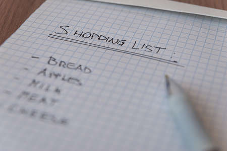 Shopping list, written on checked notepad