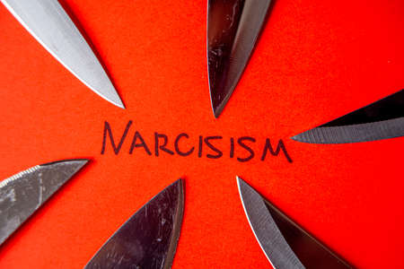 Word Narcissism, written in black on red ink, with knife blades next to it