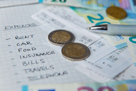 List of monthly expenses, written in pen on notepad, with receipts and money next to it Archivio Fotografico