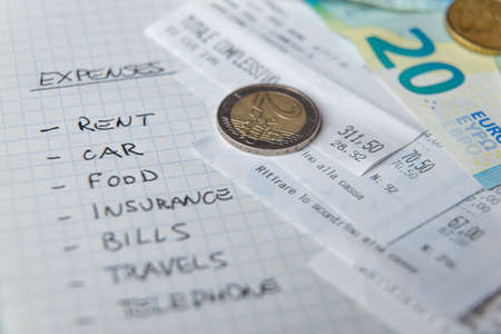 List of monthly expenses, written in pen on notepad, with receipts and money next to it