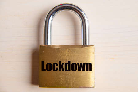 Padlock with Lockdown inscription, put on wooden surface