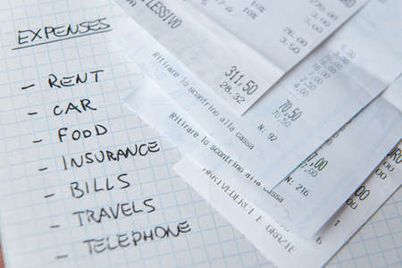 List of monthly expenses, written in pen on notepad, with receipts next to it