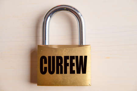 Padlock with Curfew inscription, on white wooden surface