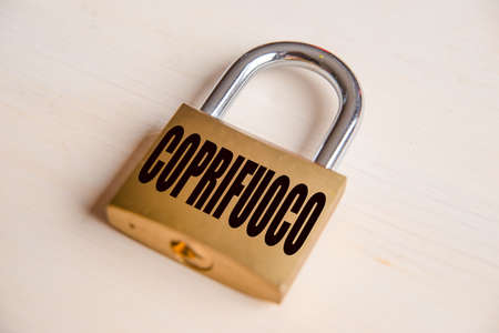Padlock with Curfew inscription in italian language, on white wooden surface