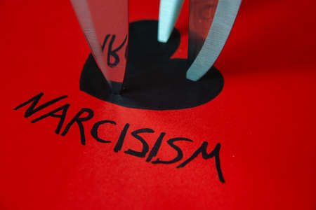 Word Narcissism, written in black on red paper, next to black heart drawing, with knife blades