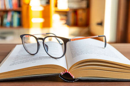 Open book, with eyeglasses on top.