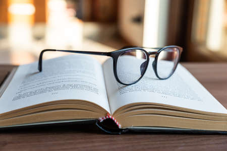 Open book, with eyeglasses on top. Banque d'images