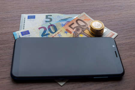 Smartphone with banknotes and coins next to it, on wooden surface. Telephone charges and payments.