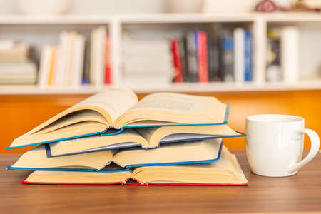 Open books, arranged one on top of the other, with a white cup of tea or coffee next to them, on a wooden surface, in front of the bookcase. Reading, studying, learning.