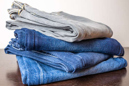 Folded jeans of various colors, arranged one on top of the other, and placed on a wooden surface.