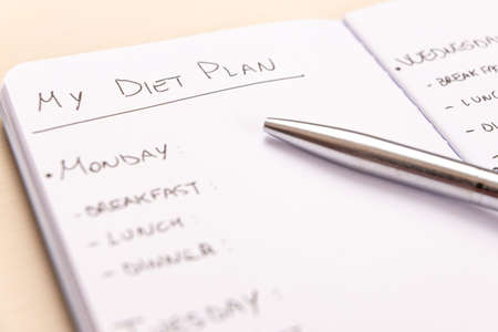 Diet plan: planning of the weekly diet, with the foods to eat during the week, written on a white notebook with black ink.