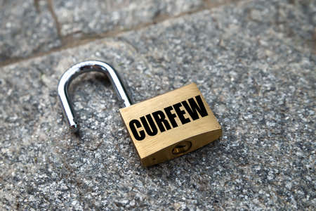 "Open padlock, with black writing ""Curfew."
