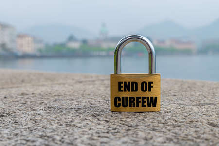 """Open padlock with black writing """"end of curfew"""" in english language."""