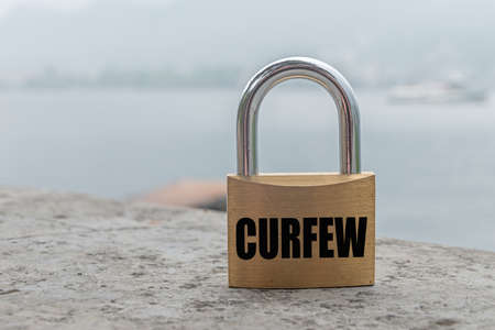 "Closed padlock with black writing ""Curfew"" in english language."