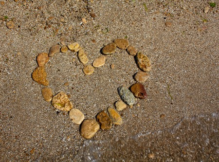 Heart from stones on sand seacoast photo