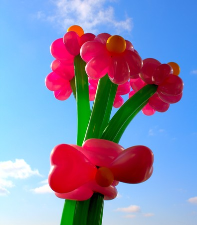 Inflatable flowers against the sky and clouds Stock Photo