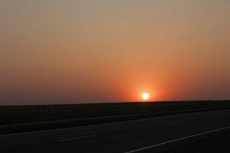 Sunrise over road and a field Stock Photo - 7542390