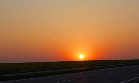 Sunrise over road and a field Stock Photo - 7542386