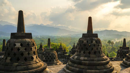 Glorious sunset at Borobudur Temple in East Java, Indonesia. Blue and orange sky over the hills, green jungles and stupa, travel destination.