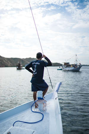 Komodo, Indonesia - August 6, 2016: a captain of the boat stands on the front deck and looking in the sea. Man fishing on the sea, fishing on the lake. Soft focus