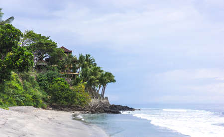 Beautiful beach in Indonesia with green palm trees and resort on the cliff, cloudy weather in the sea, travel vacation concept