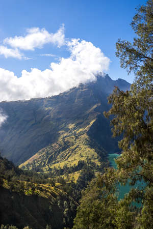 Mountains and green phosphor river, landscape with clouds in the morning, beautiful volcano Rinjani Gurung at Lombok Island, Indonesia. Small lake in the mountains, soft focus