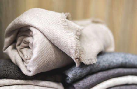 pile of clothes, rolled beige cashmere blanket, Knitting cashmere wool yarn, closeup beige blanket, home decor, closeup rolled beige cashmere woollen blanket