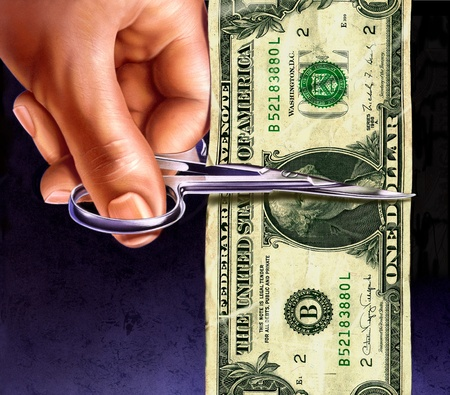 one dollar note being cut by scissors in hand photo