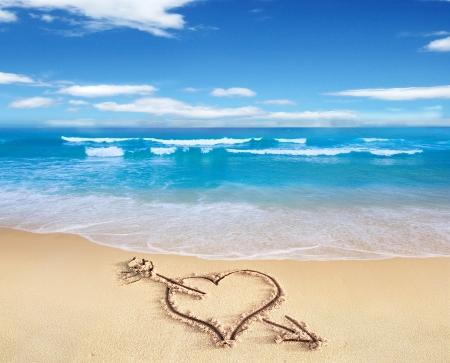 Srdce se šipkou, jak láska znamení, vypracované na pláži břehu, s See a oblohou v pozadí.