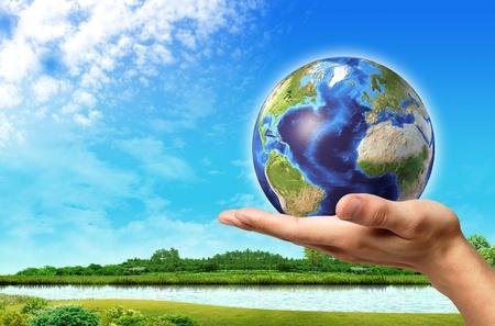 Man hand met wereldbol erop en een prachtig groen landschap met rivier en blauwe hemel, op de achtergrond.