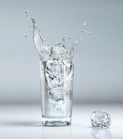 Cube de glace éclaboussures dans un verre plein d'eau Banque d'images - 11779785