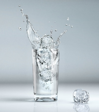 ice cube splashing into a glass full of water