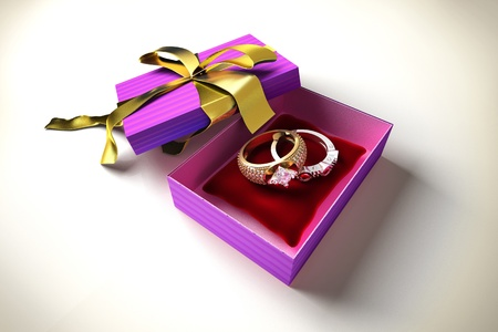 Opened gift box with golden ribbon, with two precious rings, on a red pillow inside  photo