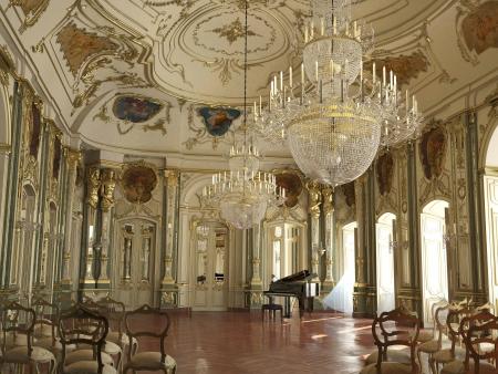 Majestueuze grote versierde piano concertzaal met gouden versieringen, beeldhouwwerken, fresco's en kroonluchters