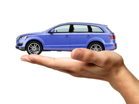 car garage: Human hand with a car on the palm. Isolated on white background, with clipping path.