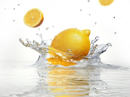 lemon splashing into clear water on white background. Imagens