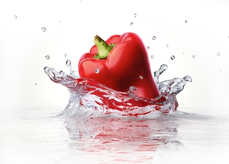 Red sweet bell pepper falling and splashing into clear water. Imagens