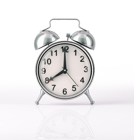 Classic Alarm clock chromed, front view on white background, with slight reflection on the surface. Hands at 8 o clock. Clipping path included. Imagens