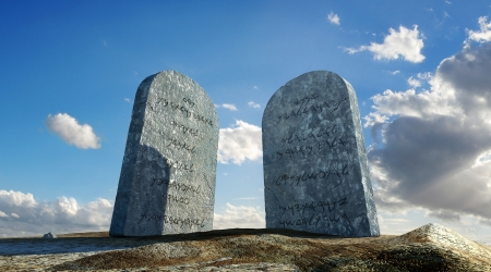 Ten commandments stones, viewed from ground level in dramatic perspective, with sky and clouds in background  Imagens