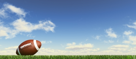 fields: American football ball, on the grass, with fluffy couds sky in the background. Side view, from ground level, panoramic format. Stock Photo