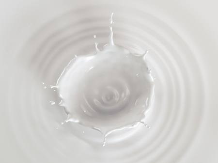 Milk crown splash in milk pool with circular ripples viewed from the top.