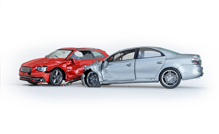 Two cars accident. Crashed cars. One silver sedan against one red coupé. Big damage. Isolated on white background. Viewed from a side.