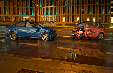 Two cars accident. Crashed cars on the road on city location at night time. A blue sedan against a red city car. Frontal collision with big damages.